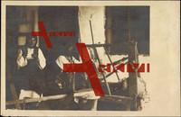 Zwei Frauen in Tracht sitzen vor dem Webstuhl