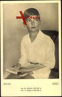 Prinz Peter II von Jugoslawien, sitzend mit Buch in der Hand