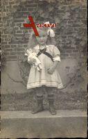 Kleines Mädchen in weißem Kleid, Haarschleife, Puppe, Spielzeug