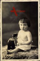 Kleinkind mit Puppe sitzt auf einem Tierfell, Spielzeug