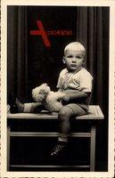 Kleiner blonder Junge mit Spielzeug, Teddybär