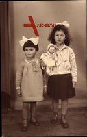 Zwei junge Kinder mit Spielzeug, Puppe, Haarschleifen