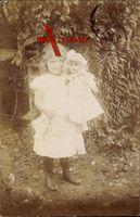 Kleines Mädchen mit einer Puppe im Arm, Spielzeug