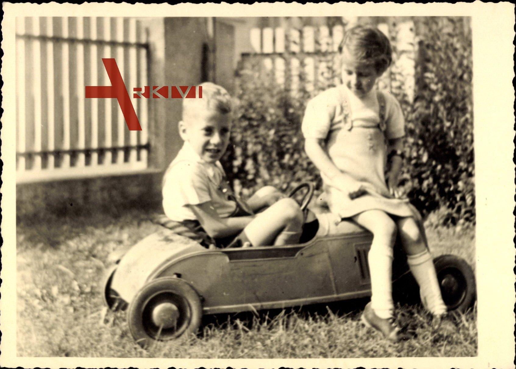 Zwei kleine Kinder in einem Spielzeugauto, Spielzeug