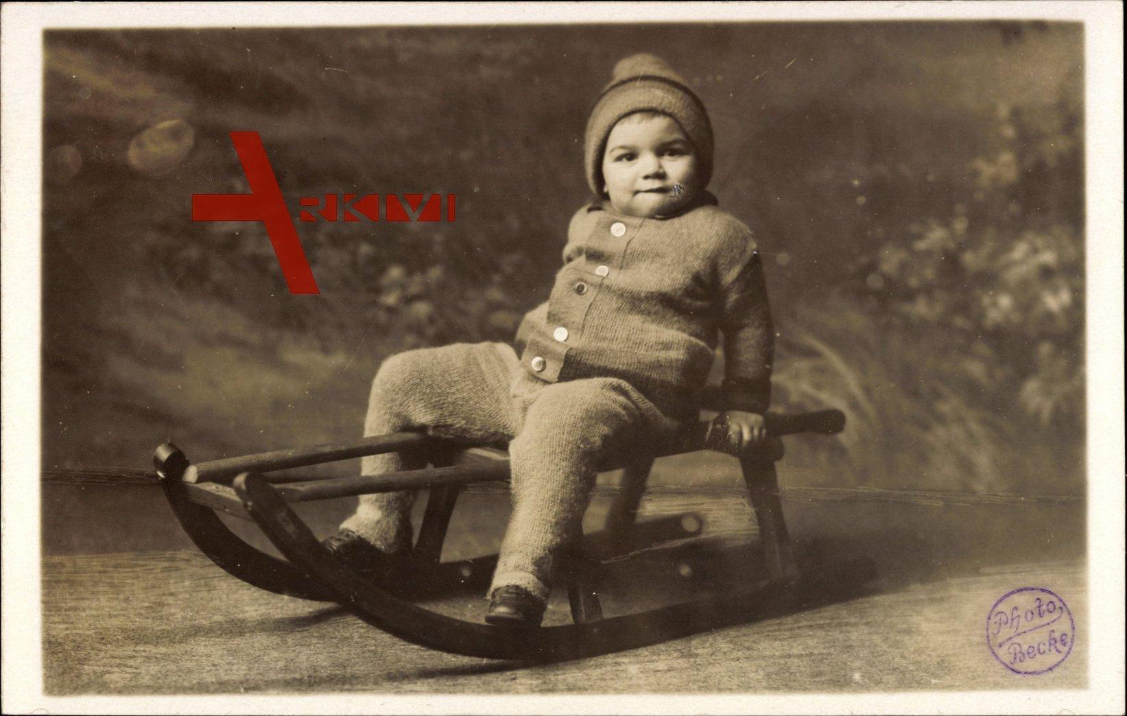 Kleiner junge auf einem Holzschlitten, Sitzportrait, Winterkleidung