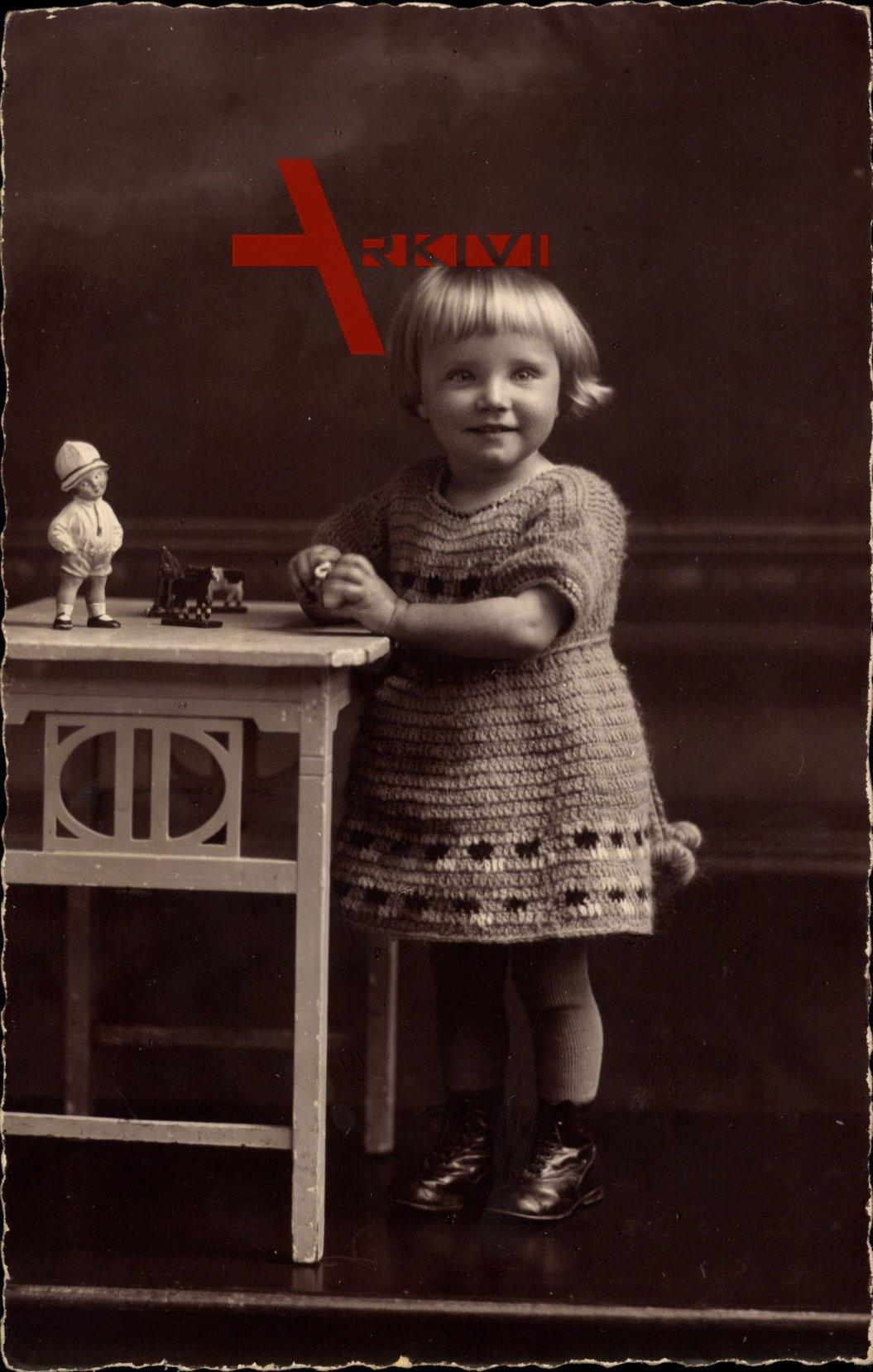 Kleines Mädchen mit ihrem Spielzeug, Wollpullover, Standportrait
