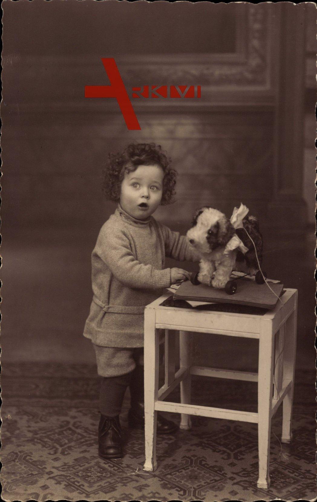 Kleinkind mit seinem Spielzeug, Teddy auf Rädern, Tisch