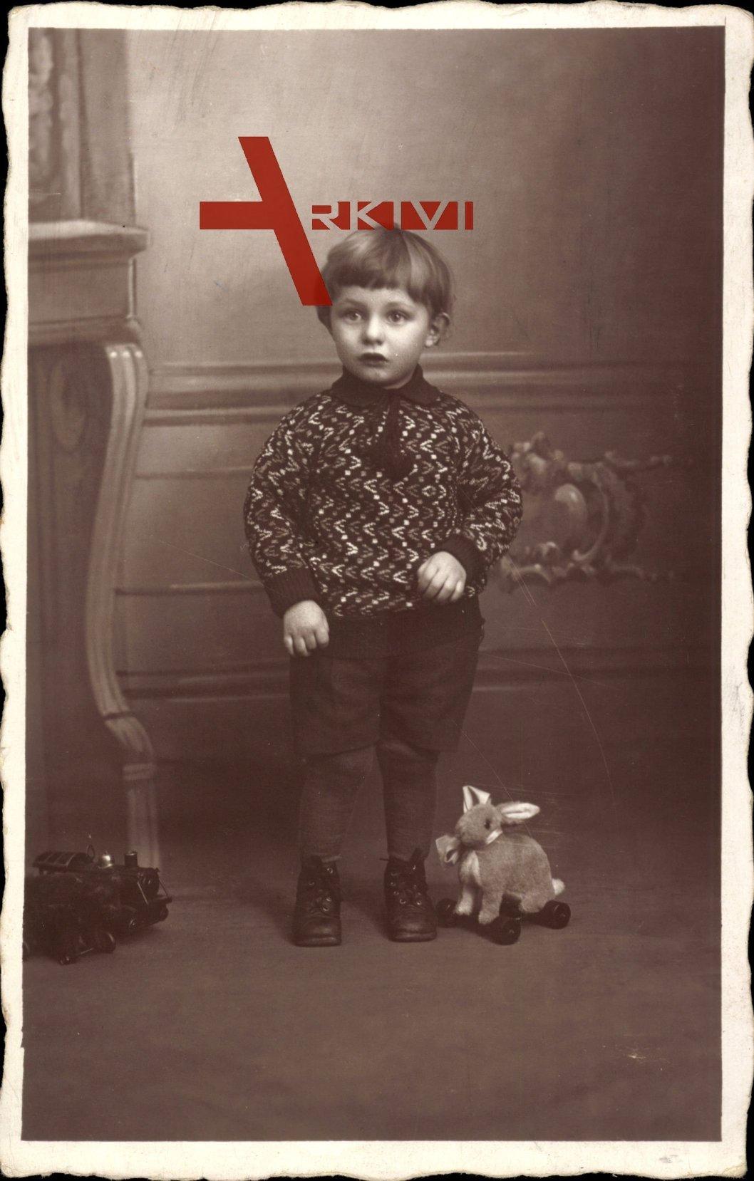 Kleinkind mit einem Hasen auf Rädern, Spielzeug, Standportrait