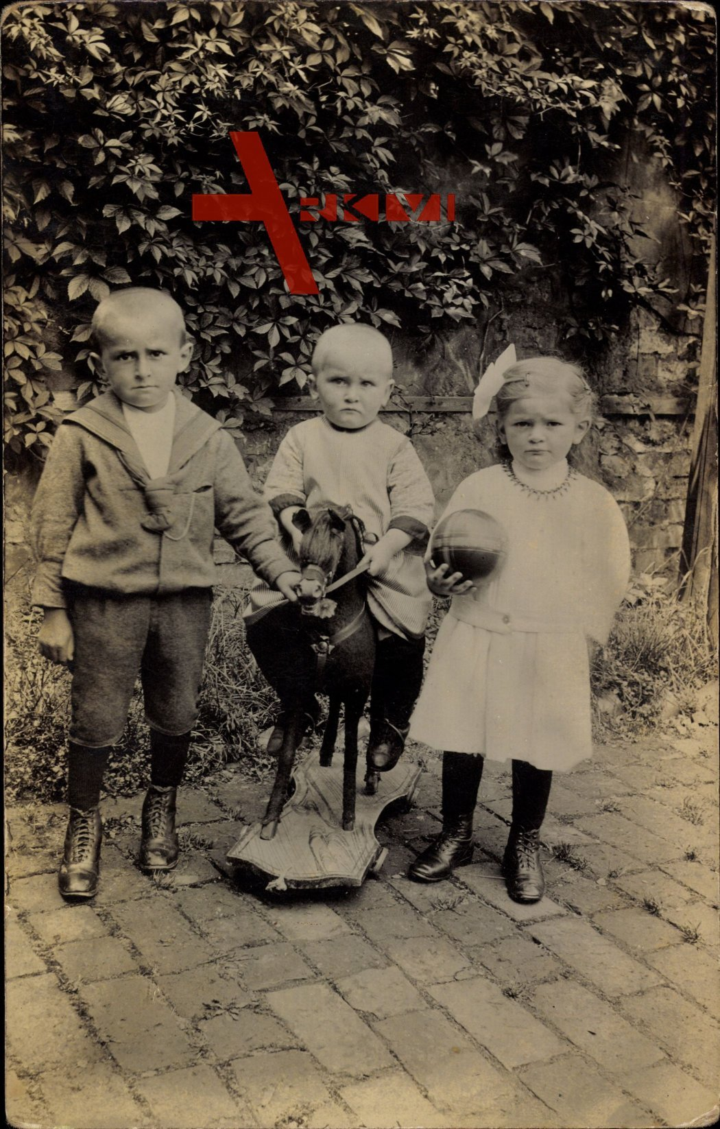 Drei kleine Kinder mit Spielzeug, Schaukelpferd, Ball