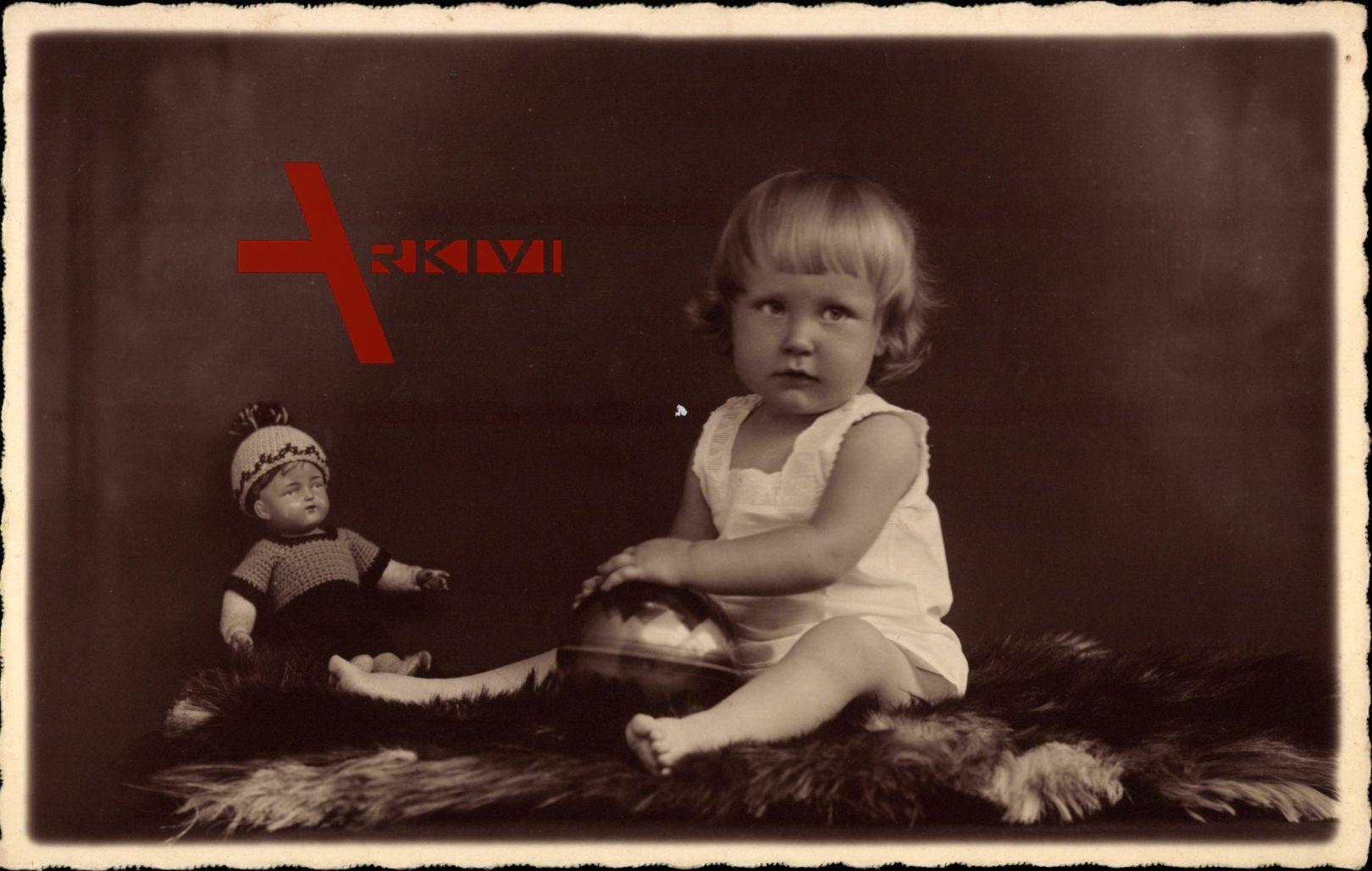 Kleinkind auf einer Pelzdecke, Puppe, Spielzeug