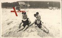 Zwei junge Mädchen spielen am Strand im Sand