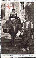 Mallorca, Frau in Tracht mit Korb auf Esel geführt von Mann