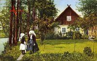 Burg im Spreewald, Blick auf ein haus und Frauen in Tracht, Fluss