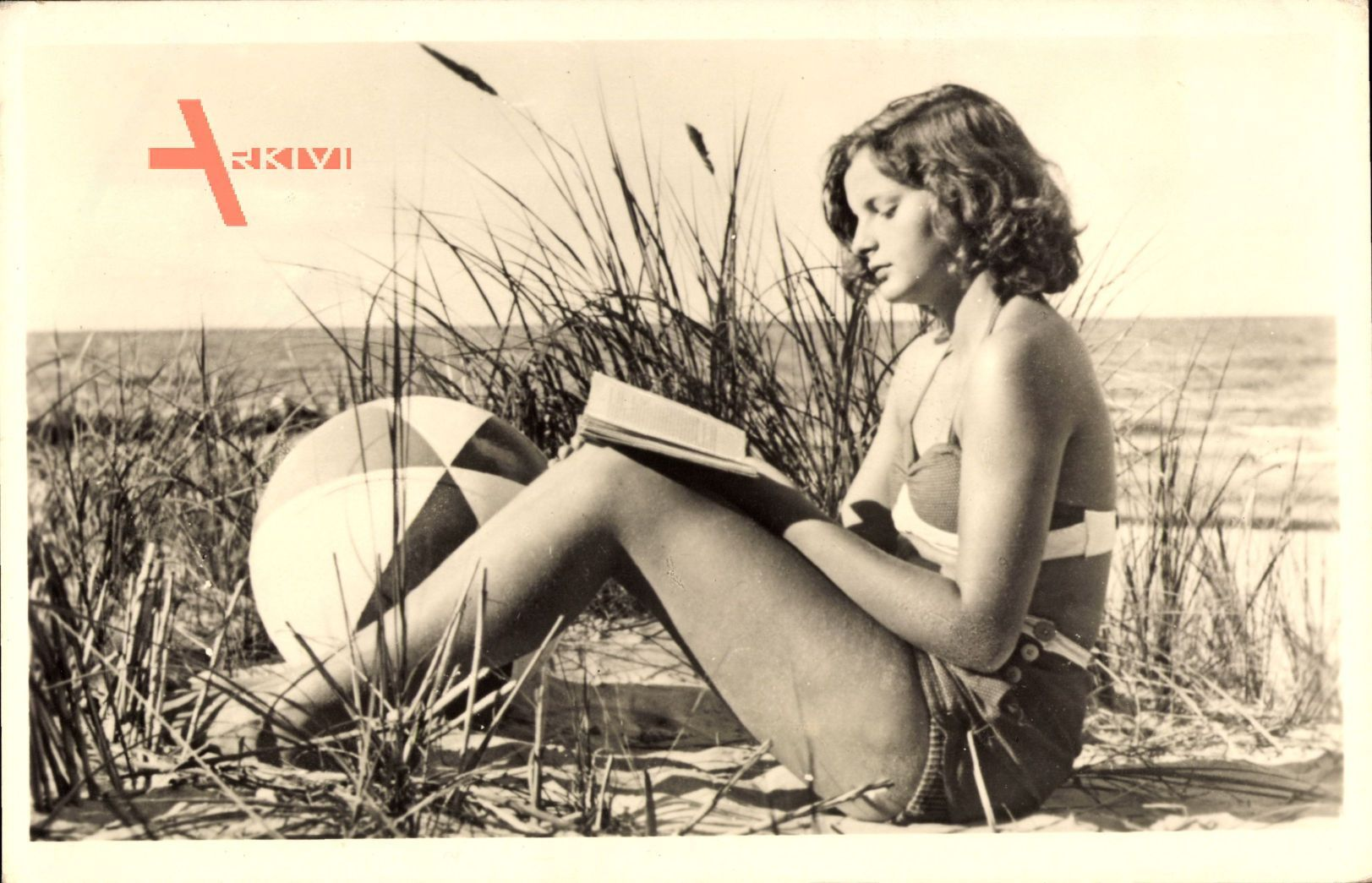 Junges Mädchen in Badekleid am Strand, Buch lesend, Spielball, Meer
