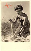 Junge Frau am Strand, Sand in der Hand, Gelocktes Haar