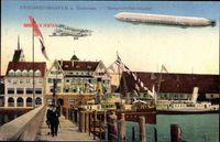 Blick auf Dampfschifffahrtshafen von Friedrichshafen am Bodensee mit Zeppelin und Doppeldecker