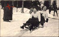 Zwei Frauen fahren auf einem Schlitten den Berg hinab, Wintersport