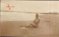Männerstrand, Junger Mann in gestreiftem Badekleid