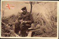 Deutscher Soldat schreibt einen Feldpostbrief im Feld