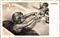 Kleinkind spielt mit einer Puppe in der Badewanne