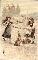 Glückwunsch Ostern, Mädchen spielen mit Osterhasen auf der Weide